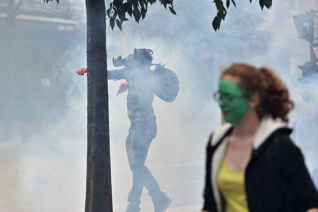 A protestor throws back a tear gas canister to police during a demonstration against France's Socialist government's labour reforms on September 15, 2016, in Paris. (Photo by Christophe Archambault/AFP Photo)