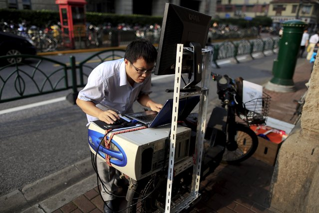 """Yue Banghai checks on his laptop on the back of his electric bike at a """"street stock salon"""" in central Shanghai, China, September 5, 2015. Yue is a businessman who's been selling futures and stock analysis software for five years. (Photo by Aly Song/Reuters)"""