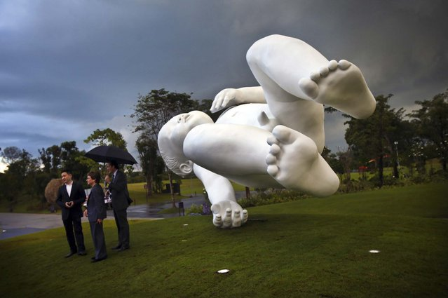 "A giant sculpture of a baby titled ""Planet"" is unveiled at the Gardens By The Bay in Singapore, January 18, 2013. British artist Marc Quinn created the work of art in 2008. (Photo by Wong Maye-E/Associated Press)"