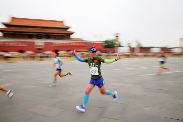A participant gestures while running past the Tiananmen gate during the Beijing Marathon in Beijing, China, September 17, 2016. (Photo by Damir Sagolj/Reuters)