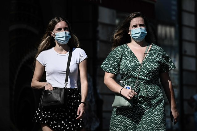 Pedestrians wearing protective face masks due to the COVID-19 disease caused by the novel coronavirus, walk in a street of Bordeaux, southwestern France, on September 14, 2020. (Photo by Philippe Lopez/AFP Photo)