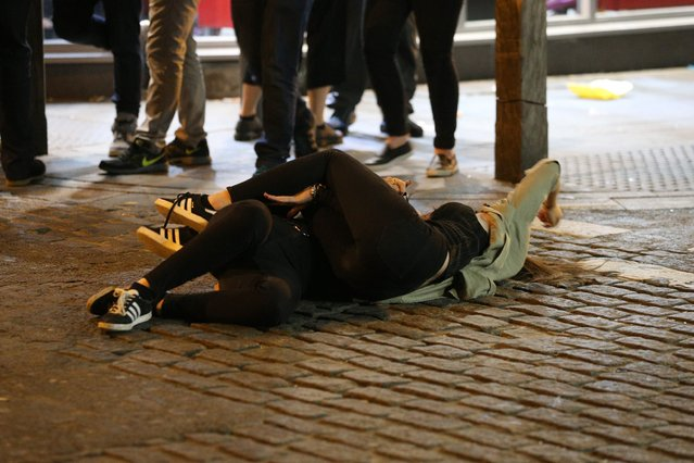 A pair have a hug in the Liverpool road as another person joins a girl who has taken a tipsy tumble in Liverpool, United Kingdom on September 21, 2016. (Photo by Paul Jacobs/FameFlynet UK)