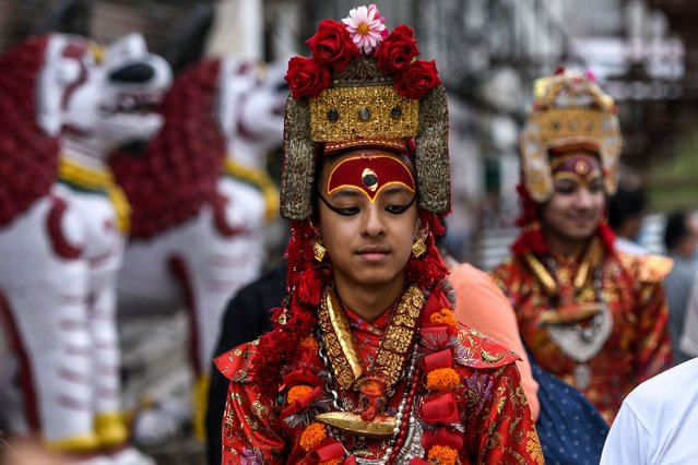 "Devotees dressed as Hindu deities Ganesh (L) and Bhairav (C) return from the living goddess Kumari's house as large gatherings are restricted due to Covid-19 coronavirus measures for the annual Indra Jatra festival, at Hanuman Dhoka area in Kathmandu on August 30, 2020. The eight-day long festival ""Indra Jatra"" celebrates the Hindu king of gods and god of rains Indra and is also usually marked by the Kumari Jatra, the religious procession of the living goddess Kumari. (Photo by Prakash Mathema/AFP Photo)"