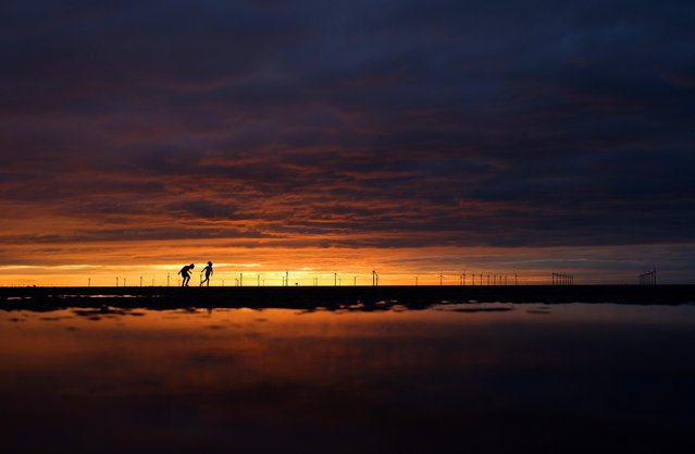 Children run along the beach at sunset in New Brighton, Britain, August 6, 2020. (Photo by Phil Noble/Reuters)