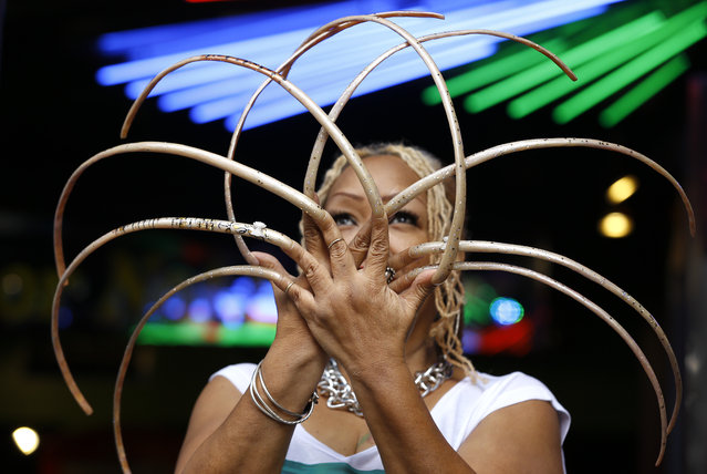 """Ayanna Williams displays her 23 inch (58 centimeter) nails at a book launch in London, Wednesday, November 19, 2014. The 56 year old stars in a book entitled """"Ripley's Believe it or Not! 2015 Annual, Reality Shock"""", a compendium of strange but true facts and stories. (Photo by Kirsty Wigglesworth/AP Photo)"""