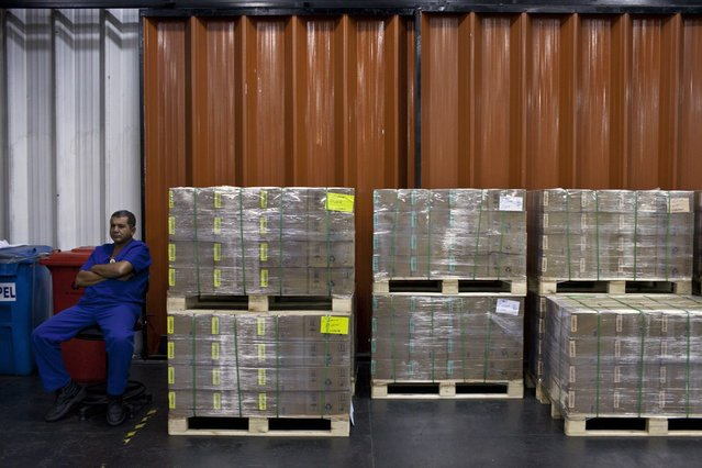 A worker sits next to boxes of Brazilian real coins ready to be shipped at the Casa da Moeda, the national mint, in the Santa Cruz suburb of Rio de Janeiro, Brazil, on Tuesday, March 5, 2013. Brazil is likely to keep its key interest rate at a record low for the third straight meeting, as policy makers are caught between a fragile economic recovery and faster-than-expected inflation. (Photo by Dado Galdieri/Bloomberg)
