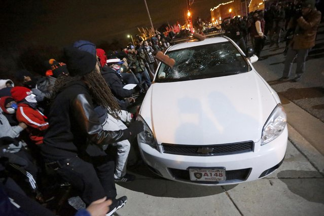 Protesters vandalize a police car outside the Ferguson Police Department in Ferguson, Missouri, after a grand jury returned no indictment in the shooting of Michael Brown November 24, 2014. (Photo by Jim Young/Reuters)