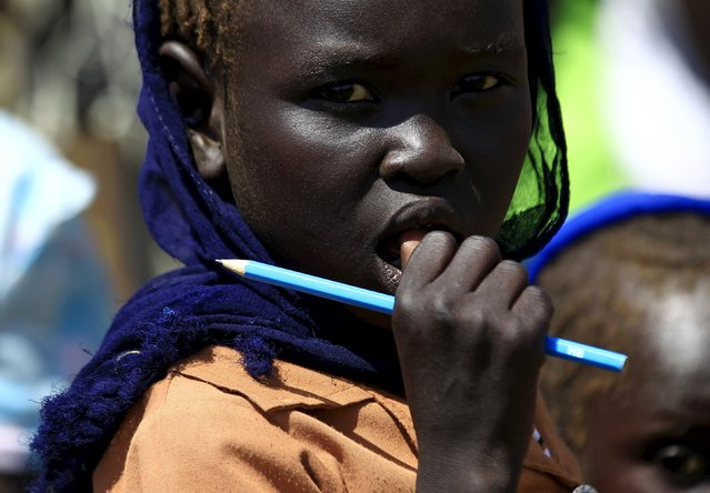 A girl waits to receive food provided by the United Nations' World Food Programme (WFP) during a visit by a European Union delegation, at an IDP camp in Azaza, east of Ad Damazin, capital of Blue Nile state, October 21, 2015. (Photo by Mohamed Nureldin Abdallah/Reuters)