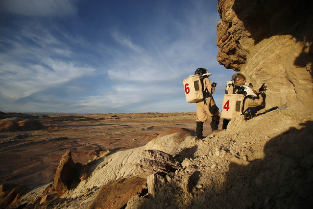 Members of Crew 125 EuroMoonMars B mission collect geologic samples for study at the Mars Desert Research Station (MDRS) in the Utah desert March 2, 2013. The MDRS aims to investigate the feasibility of a human exploration of Mars and uses the Utah desert's Mars-like terrain to simulate working conditions on the red planet. Scientists, students and enthusiasts work together developing field tactics and studying the terrain. All outdoor exploration is done wearing simulated spacesuits and carrying air supply packs and crews live together in a small communication base with limited amounts of electricity, food, oxygen and water. Everything needed to survive must be produced, fixed and replaced on site. (Photo by Jim Urquhart/Reuters)