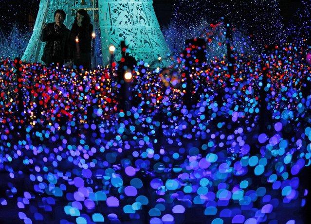 People enjoy an annual yearend illumination in Shiodome district in Tokyo, Japan, Monday, November 24, 2014. (Photo by Shuji Kajiyama/AP Photo)