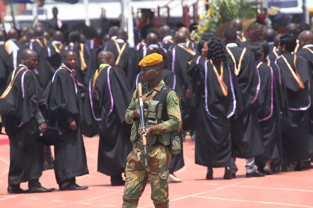 An armed soldier stands in front of University of Zimbabwe students waiting to be capped by Zimbabwean President Robert Mugabe at a graduation ceremony in Harare, Thursday, September 29, 2016. (Photo by Tsvangirayi Mukwazhi/AP Photo)