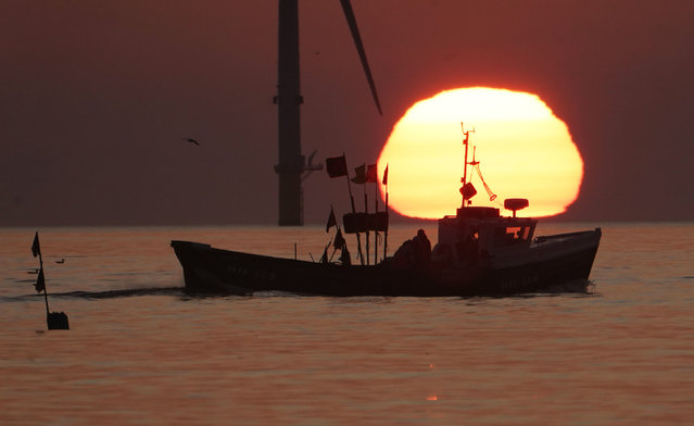 A fishing boat sails in front of the rising sun near Blyth pier in Northumberland on September 14, 2020, at the start of a week in which the UK is expected to bask in temperatures of more than 30C. (Photo by Owen Humphreys/PA Images via Getty Images)