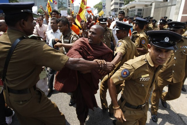 A Buddhist monk pushes police officers as they march towards the Indian High Commission to Sri Lanka during a protest in Colombo March 19, 2013. Buddhist monks held a protest on Tuesday against two separate attacks on Sri Lankan Buddhist monks who were in Chennai for education visits, and demanded the Indian government take action on these attacks, according to the demonstrators. (Photo by Dinuka Liyanawatte/Reuters)