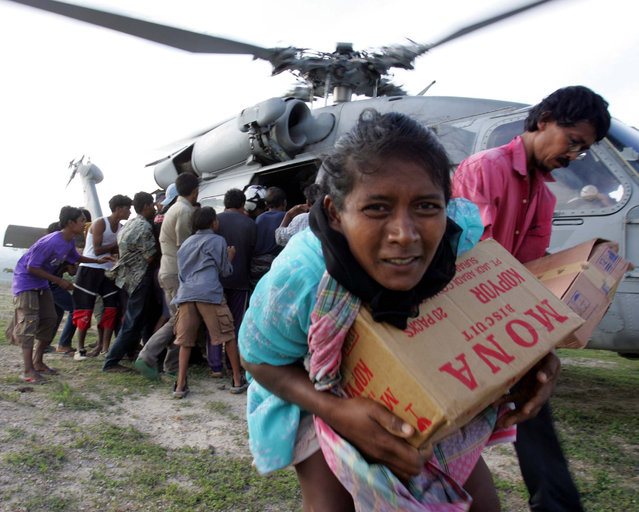 Tsunami refugees receive supplies distributed by the USS Abraham Lincoln Carrier Strike Group in Krueng Raya, northeast of Banda Aceh, Indonesia in this January 3, 2005 file photo. (Photo by Yuriko Nakao/Reuters)