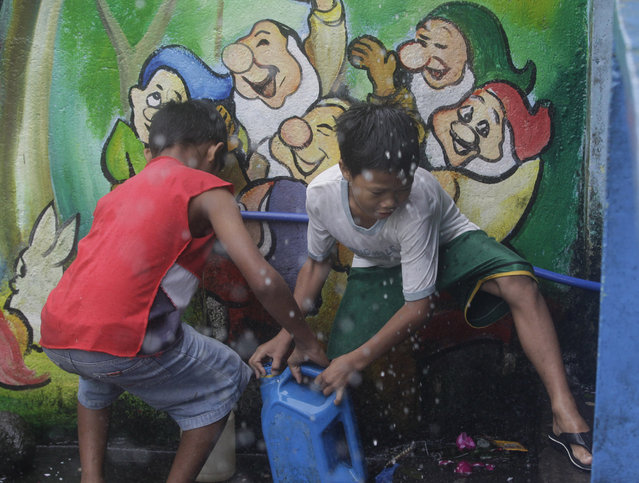 Filipino boys fetch water at a school used as an evacuation center as Typhoon Hagupit pounds Legazpi, Albay province, eastern Philippines on Sunday, December 7, 2014. (Photo by Aaron Favila/AP Photo)