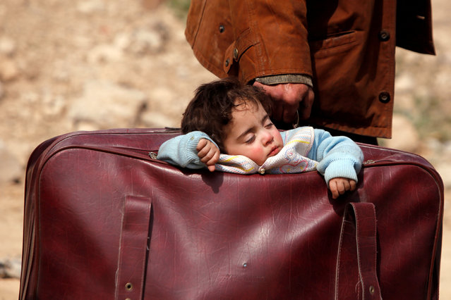 A child sleeps in a bag in the village of Beit Sawa, eastern Ghouta, Syria March 15, 2018. Thousands escaped Syria' s rebel- held Eastern Ghouta into government- held territory AFP correspondents on both sides said, the largest numbers since the regime assault on the enclave began. (Photo by Omar Sanadiki/Reuters)