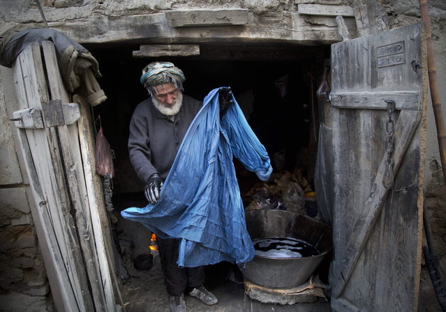Haji Hussain, 75, who colors clothing for 40 years, takes a freshly colored burqa out for drying in his small shop in the old town of Kabul, Afghanistan, Monday, April 15, 2013. (Photo by Anja Niedringhaus/AP Photo)