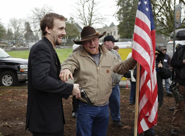 Event organizer Gavin Seim (L) poses for photos as gun rights advocates rally against Initiative 594 at the state capitol in Olympia, Washington December 13, 2014. (Photo by Jason Redmond/Reuters)