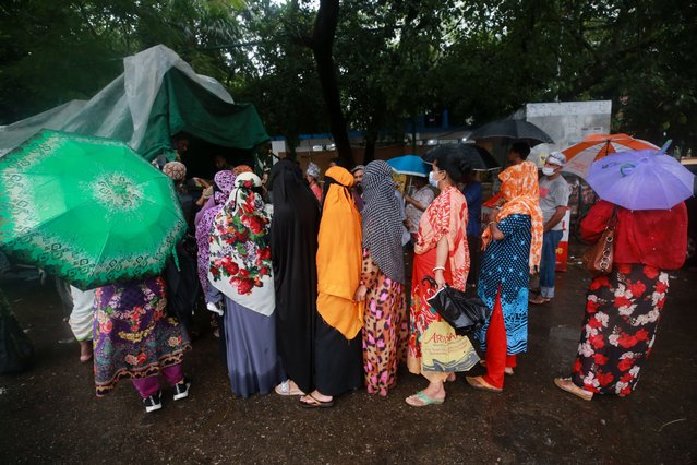 People in a queue to collect subsidised food on a rainy day in Dhaka on October 22, 2020. (Photo by Rehman Asad/NurPhoto via Getty Images)