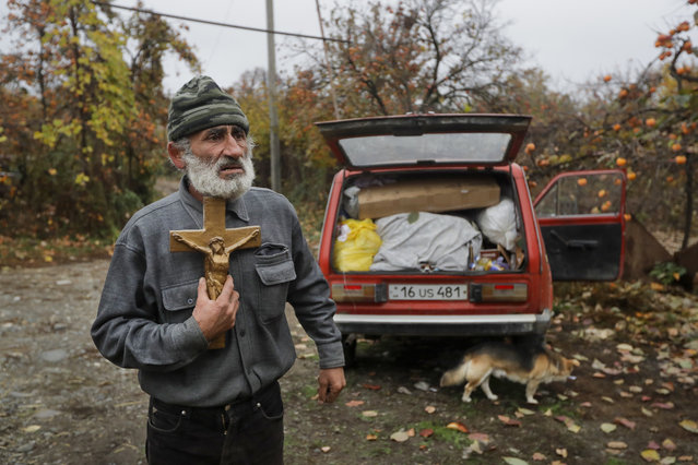 Nikolai Karapetyan reacts and presses the cross to his chest, with his car packed as he prepares to abandon his home in the village of Maraga, in the Martakert area, in the separatist region of Nagorno-Karabakh, Wednesday, November 18, 2020. (Photo by Sergei Grits/AP Photo)