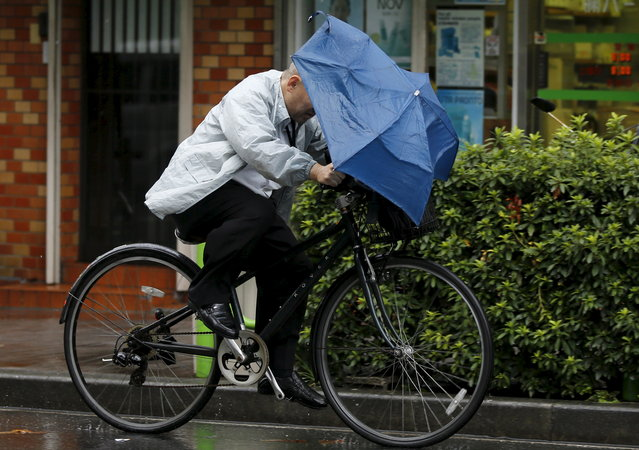 A man holding onto an umbrella as he cycles in heavy rain caused by typhoon Etau in Tokyo's business district September 9, 2015. (Photo by Toru Hanai/Reuters)