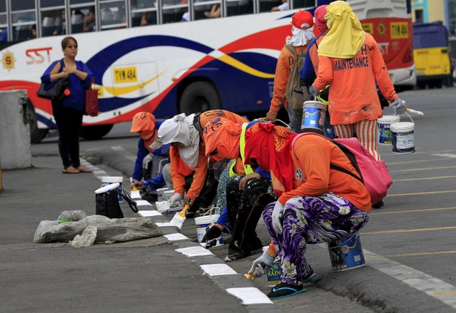Government workers re-paint the sidewalks of a main street at Roxas boulevard, metro Manila, November 9, 2015, as part of a clean-up project in preparation for the upcoming Asia-Pacific Economic Cooperation (APEC) summit meeting in Manila on November 18-19. (Photo by Romeo Ranoco/Reuters)