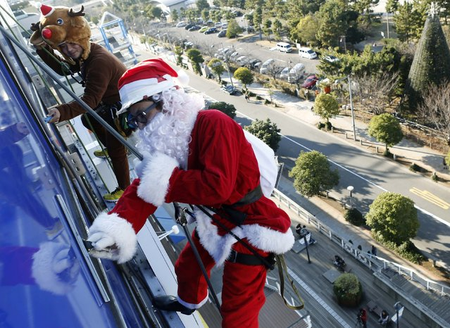 Window cleaners dressed as Santa Claus and a reindeer work during an event to celebrate Christmas at a shopping mall in Tokyo December 24, 2014. (Photo by Yuya Shino/Reuters)