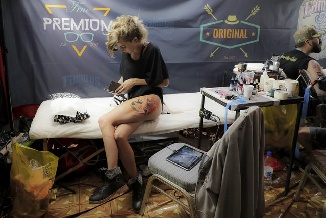A woman pauses from getting a new tattoo during the International Tattoo Convention Bucharest 2016 in Bucharest, Romania, Sunday, October 16, 2016. (Photo by Vadim Ghirda/AP Photo)