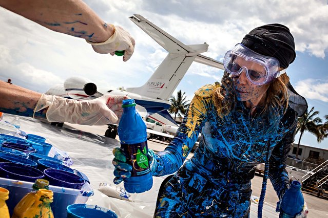 Von Anhalt reloads a blue painting bottle. (Photo by Thomas Cordy/The Palm Beach Post)