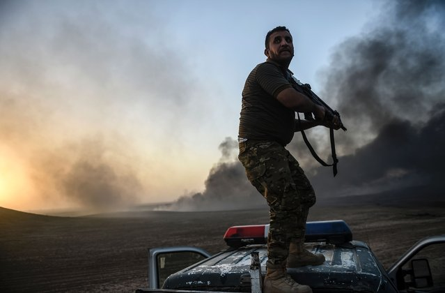 A member of the Iraqi government forces takes a position on top of a vehicle as smoke rises on the outskirts of the Qayyarah area, some 60 kilometres (35 miles) south of Mosul, on October 20, 2016, during an operation against Islamic State (IS) group jihadists to retake the main hub city In the biggest Iraqi military operation in years, forces have retaken dozens of villages, mostly south and east of Mosul, and are planning multiple assaults for October 20. (Photo by Bulent Kilic/AFP Photo)