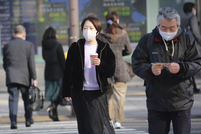 People wearing face masks to protect against the spread of the coronavirus walk on the street in Tokyo, Monday, December 14, 2020. (Photo by Koji Sasahara/AP Photo)