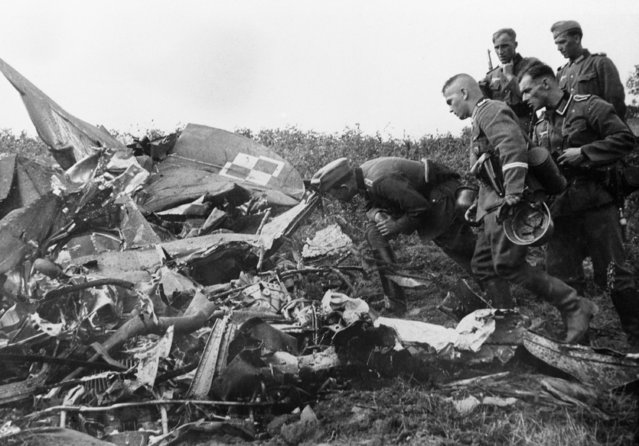 German soldiers inspect the wreckage of a Polish army plane shot down by a German pilot during an air raid, September 8, 1939. (Photo by AP Photo)