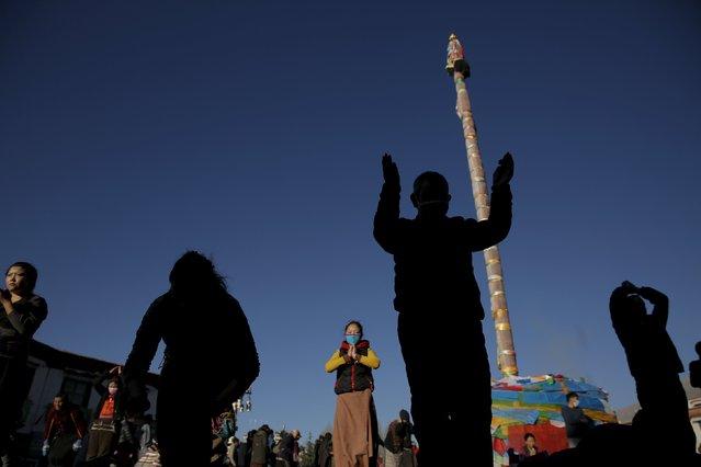 Pilgrims pray at the Jokhang Temple in central Lhasa, Tibet Autonomous Region, China as sun rises November 20, 2015. (Photo by Damir Sagolj/Reuters)