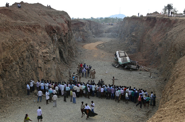 People stand behind a police cordon near the wreckage of a bus that fell into a gorge in Penukonda, about 145 kilometers north of Bangalore, India, Wednesday, January 7, 2015. The passenger bus veered off a road in southeastern India and fell into the gorge on Wednesday, killing at least 16 people, most of them college and middle school students, police said. More than 50 other people were injured in the accident. (Photo by Aijaz Rahi/AP Photo)