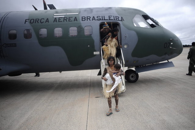 Munduruku Indians, many of who had never been in a plane, disembark from a Brazilian Air Force plane as they arrive for talks with the government, June 4, 2013. Air Force planes flew 144 Munduruku Indians to Brasilia for talks to end a week-long occupation of the controversial Belo Monte dam on the Xingu River, a huge project aimed at feeding Brazil's fast-growing demand for electricity. (Photo by Ueslei Marcelino/Reuters)