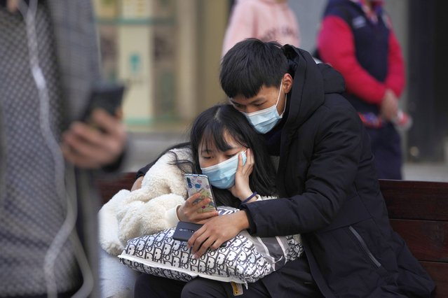 A man and woman wearing masks to help protect themselves from the coronavirus share a smartphone on the street in Wuhan in central China's Hubei province on Thursday, January 14, 2021. A global team of researchers for the World Health Organization arrived Thursday in the Chinese city where the coronavirus pandemic was first detected to conduct a politically sensitive investigation into its origins amid uncertainty about whether Beijing might try to prevent embarrassing discoveries. (Photo by Ng Han Guan/AP Photo)
