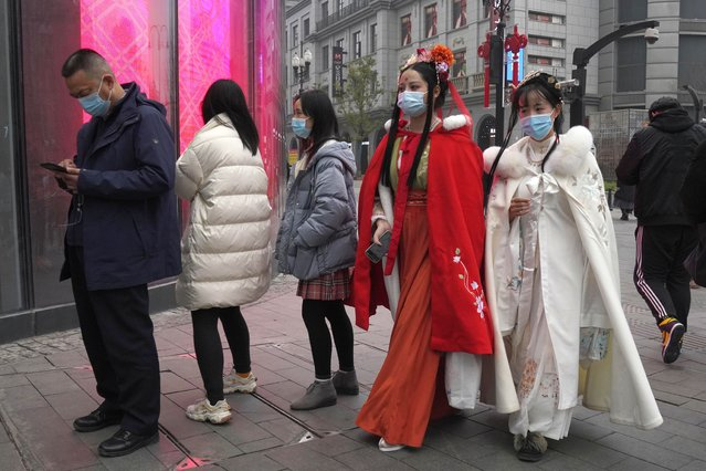Chinese women dressed in traditional costumes and wearing masks visit a popular shopping street in Wuhan in central China's Hubei province, Saturday, January 23, 2021. A year after it was locked down to contain the spread of coronavirus, the central Chinese city of Wuhan has largely returned to normal, even as China continues to battle outbreaks elsewhere in the country. (Photo by Ng Han Guan/AP Photo)
