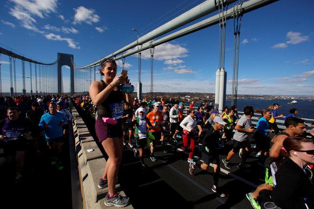 A runner stops to take a photo on the Verrazano–Narrows Bridge during the 2016 New York City Marathon in the Manhattan borough of New York City, NY, U.S. November 6, 2016. (Photo by Brendan McDermid/Reuters)