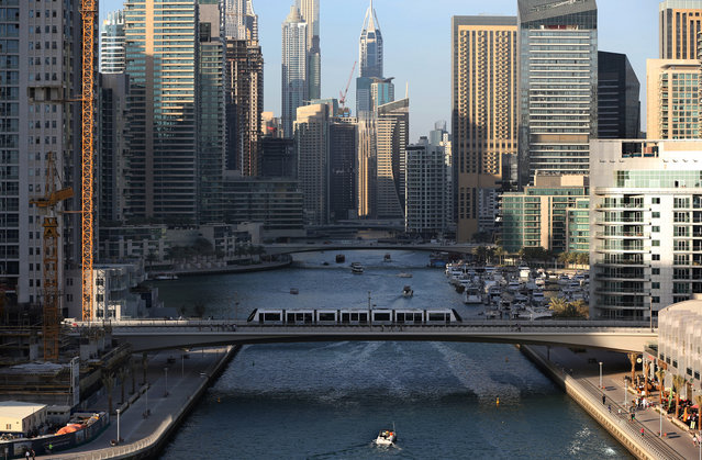 In this April 1, 2015 photo, a tram crosses a bridge over a  canal that forms the Marina waterfront district of Dubai, United Arab Emirates. The Marina neighborhood is one of many clusters of neck-bending skyscrapers built throughout Dubai, but its real power lies behind the gated privacy of its most luxurious towers. Owning an apartment in one of these towers means access to skyline pools, concierge services and grand apartments that cater to the region's royalty, as well as the world's wealthiest businessmen and women. (Photo by Kamran Jebreili/AP Photo)