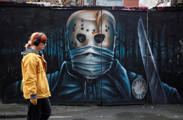 A woman walks past a mural amid the outbreak of the coronavirus disease (COVID-19) in Manchester, Britain, January 4, 2021. (Photo by Phil Noble/Reuters)