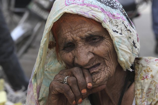 Abida Khatoon, a Pakistani vendor, who sells dry fruit to earn living for her family, waits for customers outside a shrine in Lahore, Pakistan, Thursday, October 27, 2016. (Photo by K.M. Chaudhry/AP Photo)