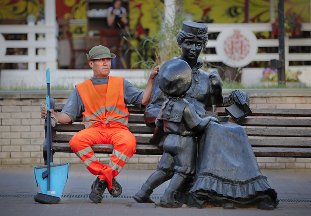 A municipal worker sits on a bench, next to a statue, in Nizhny Novgorod, Russia, during the 2018 soccer World Cup, Thursday, June 28, 2018. (Photo by Vadim Ghirda/AP Photo)