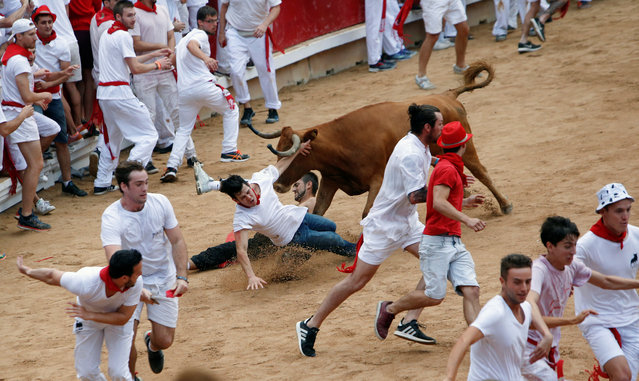A reveller is tossed by a wild cow following the first running of the bulls at the San Fermin festival in Pamplona, Spain, July 7, 2018. (Photo by Joseba Etxaburu/Reuters)