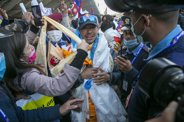 Nirmal Purja one of the team member of the all-Nepalese mountaineering team that became the first to scale Mount K2 in winter receives a scarf as they arrive at Tribhuwan International airport in Kathmandu, Nepal, Tuesday, January 26, 2021. (Photo by Niranjan Shrestha/AP Photo)