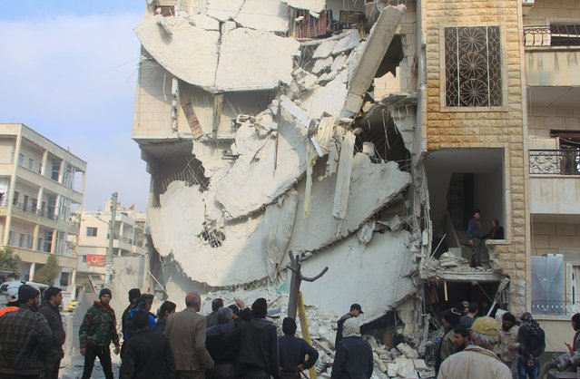People inspect a site hit by what activists said were airstrikes carried out by the Russian air force in Idlib city, Syria December 20, 2015. (Photo by Ammar Abdullah/Reuters)