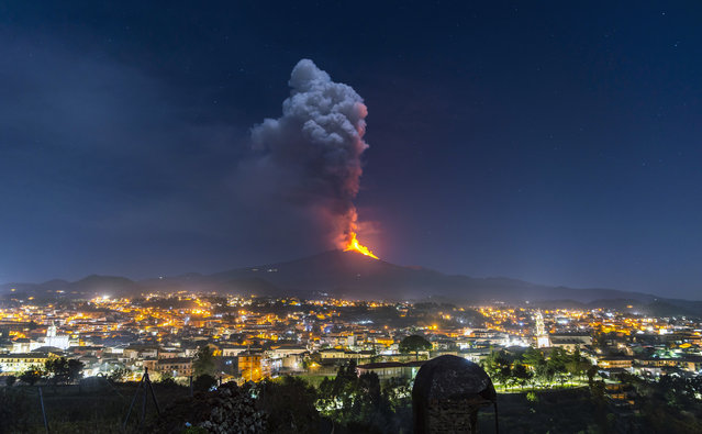 Flames and smoke billowing from a crater, as seen from the southern side of the Mt Etna volcano, tower over the city of Pedara, Sicily, Wednesday night, February 24, 2021. (Photo by Salvatore Allegra/AP Photo)