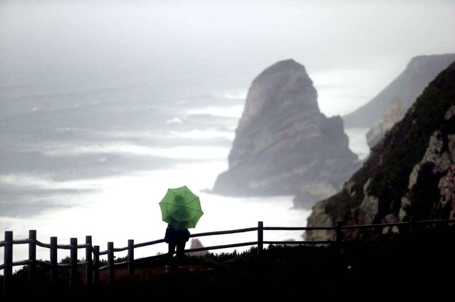 A woman shelters from the rain with an umbrella as she looks out the rough sea from atop a cliff at the Cabo da Roca, Cape Roca, near Sintra, Portugal, Thursday, January 15, 2015. The cape is the westernmost land spot of continental Europe. (Photo by Francisco Seco/AP Photo)