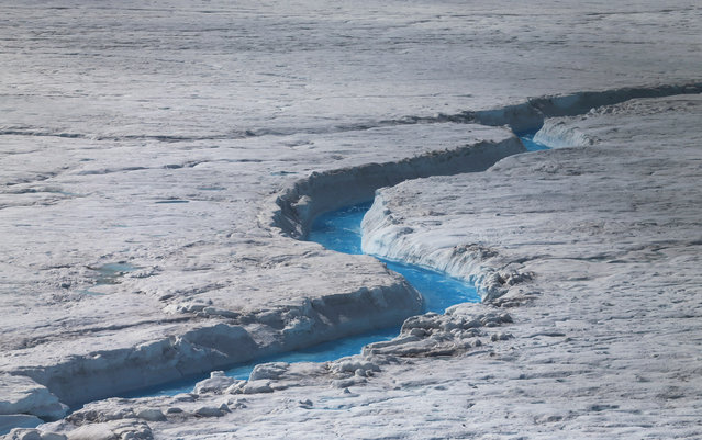 Water flows across the surface of the glacial ice sheet, photographed on July 17, 2013. (Photo by Joe Raedle/Getty Images via The Atlantic)