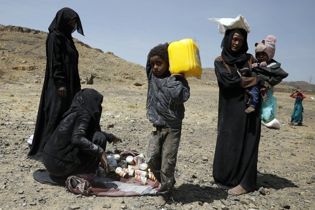 Displaced Yemenis get food rations provided by Mona Relief Yemen ahead of an international donors conference on Yemen, at a camp for Internally Displaced Persons (IDPs) in Sana'a, Yemen, 01 March 2021. The United Nations is launching an international donors conference on Yemen Humanitarian Response Plan to address a humanitarian crisis in the war-torn country, warning that over 16 million people, more than half of Yemen's population, would go hungry in 2021, with already some half a million people living in famine-like conditions. (Photo by Yahya Arhab/EPA/EFE)