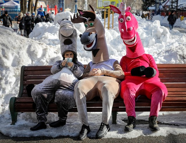 Street animators wearing fancy costumes take a break on a bench in a park in Stavropol, Russia on March 14, 2021. (Photo by Eduard Korniyenko/Reuters)